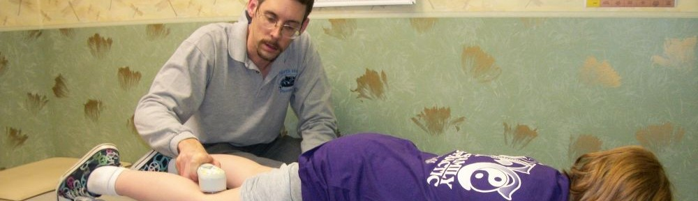 Dr. Austin using cold laser therapy on a pediatric patient.
